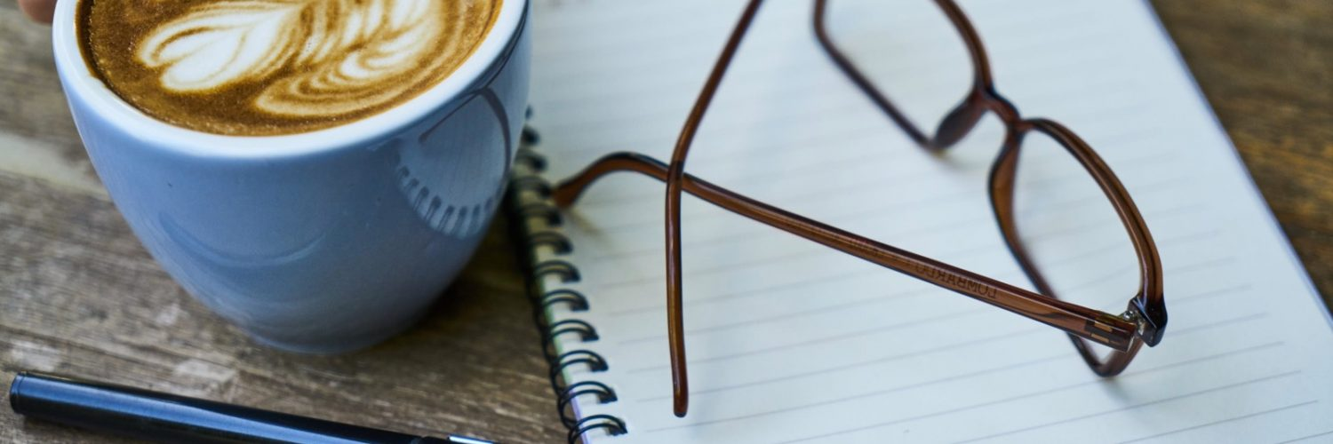 Notebook, glasses and a cappuccino