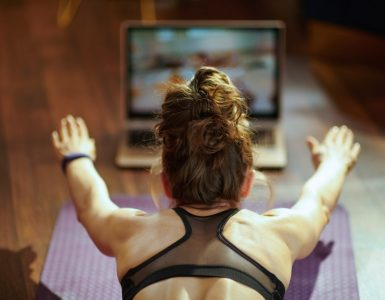 Woman doing exercises in front of a laptop