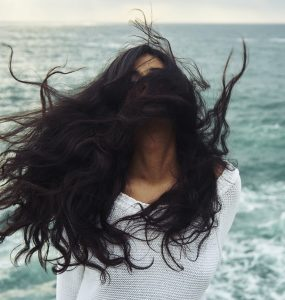 Woman with hair blowing wildly in the wind by the sea