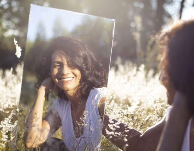 Woman outdoors looking in a mirror smiling