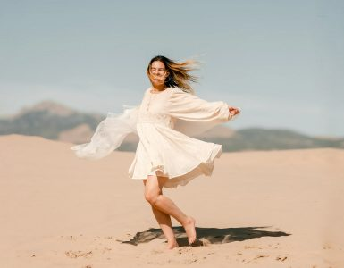 Woman in a white dress dancing on the sand