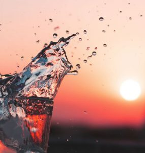 glass of water splashing in the sunset