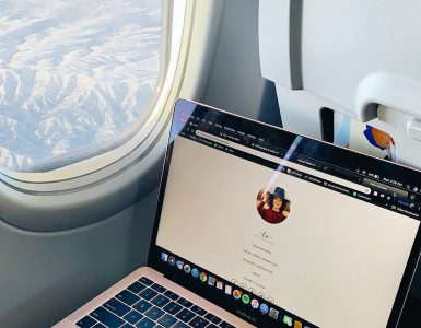 An open laptop on a plane with view of mountains