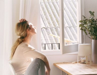 Woman sitting in kitchen facing the window