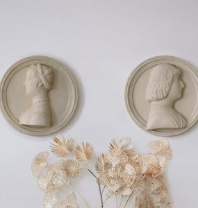 2 wall plaques of man and woman facing away from each other