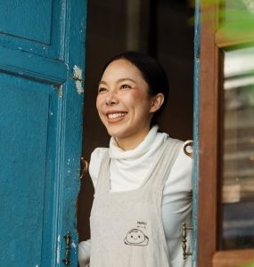woman opening door greeting a customer