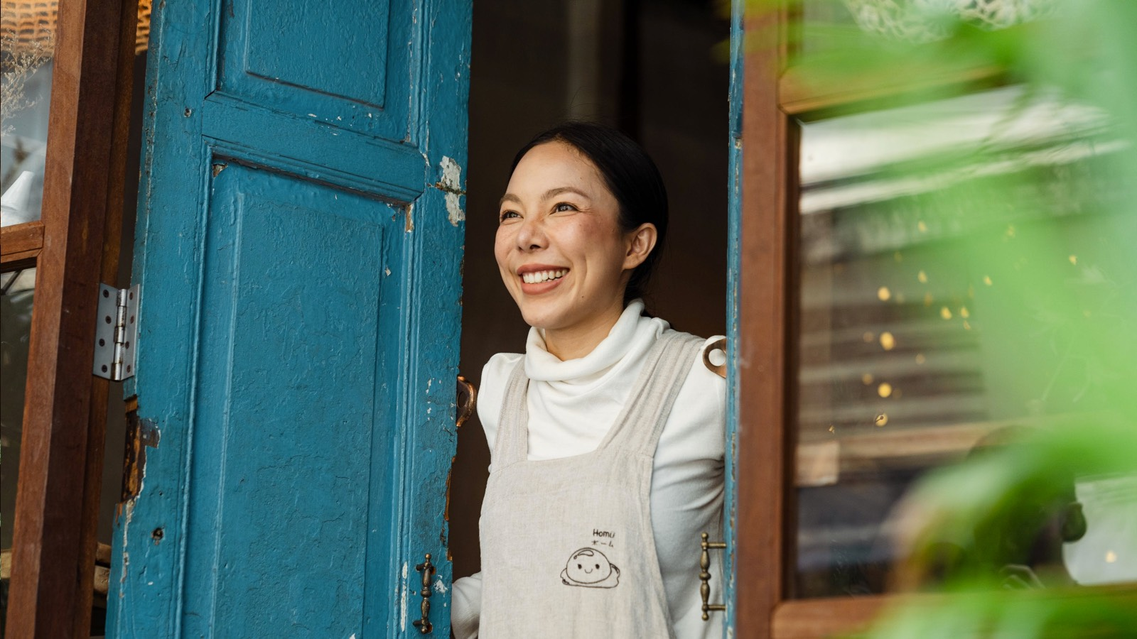 A woman opening door greeting a customer